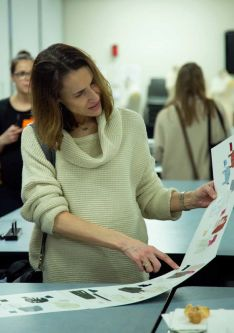 Woman in a cream jumper looking at a student work portfolio