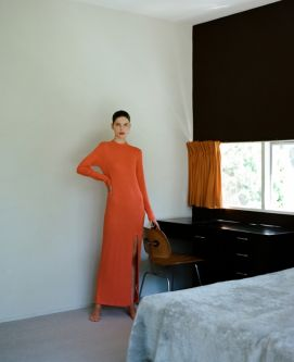 Photograph of woman standing in a bedroom wearing an orange dress