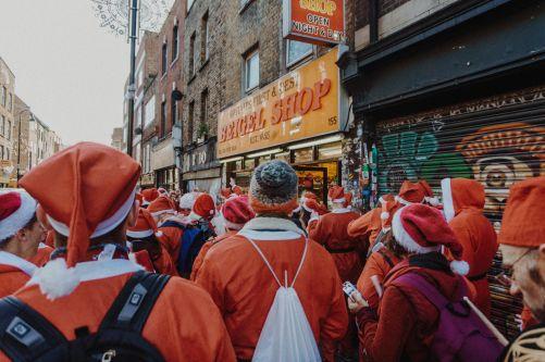 People dressed  up like santa standing outside pub