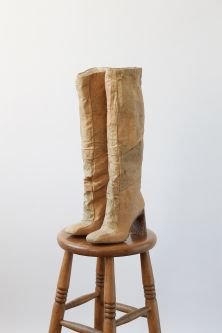 Beige knee high boots on a wooden stool