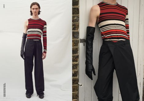 Model standing against a photographic background, wearing a sleeveless stripey top and black trousers