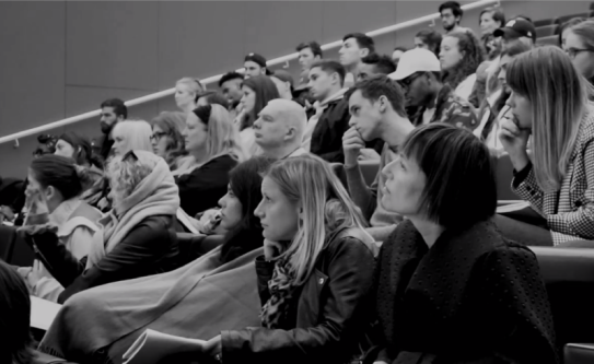 black and white image of an audience in a lecture theatre