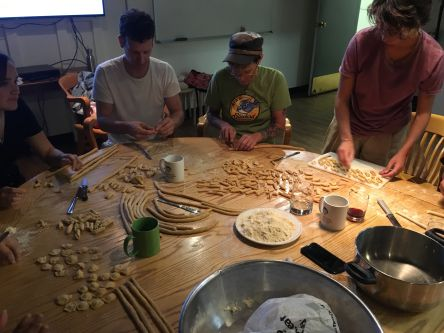 people around a table making pasta