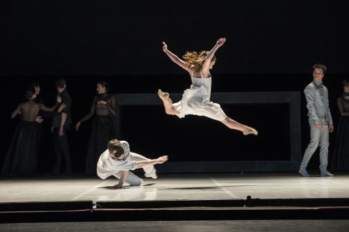 two dancers leaping in a dark theatre