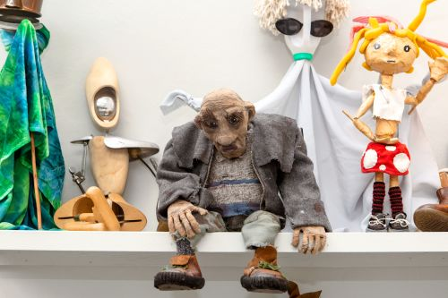 A variety of puppets sitting on a shelf as part of Emergence exhibition