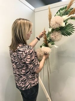 A photo of Sarah Manning standing and fixing together a floral arrangement.