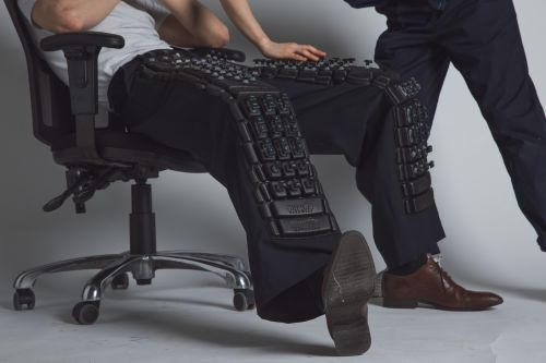 close up of model sitting in a chair, wearing trousers embellished with black embossed keyboard cut out letters and console knobs.