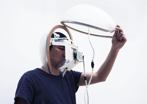 Photo of a man with a helmet on with wires coming out of it