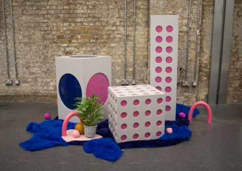 a display consisting of pink and white dotted cubes placed on a blue fabric