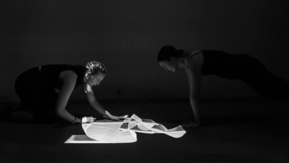 A black and white photograph of two women working on a design which is laid out on the floor