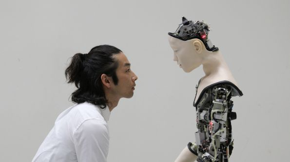 Japanese man face to face with robot both side profile
