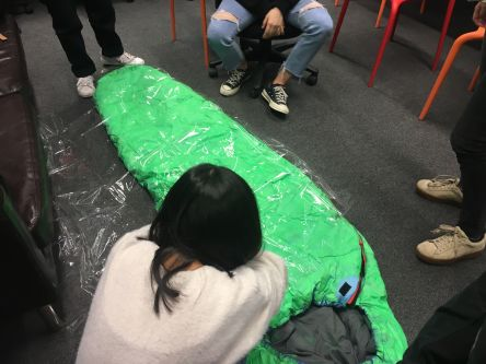Students work in progress, wrapping a green sleeping bag in clear plastic