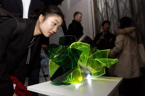 Woman looking at green perspex sculpture