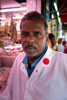 a portrait of a male in a butchers shop with red lighting