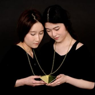two people looking at a gold object attached to chains around their neck