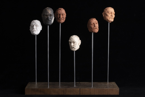 A series of heads made from clay displayed on plinths