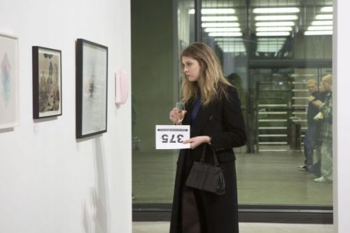 Photograph of a woman looking at the installed work in the gallery