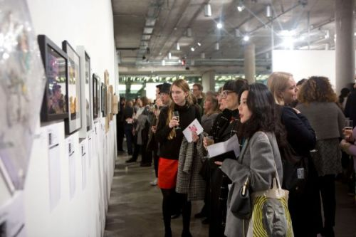 Photograph of visitors looking at art hung on the wall of a gallery