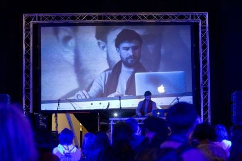 A photograph from behind a crowd watches someone DJ on stage, an image of him projected onto the screen behind him