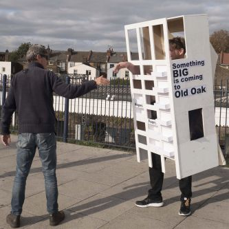 Photograph of a man shaking hands with someone dressed as a block of flats, wearing a wooden structure