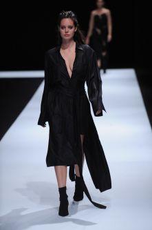 Female model wearing low cut black dress designed by Jessica Wenden