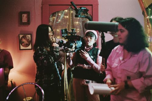 Film students with cameras and film equipment on the set of Cosmos