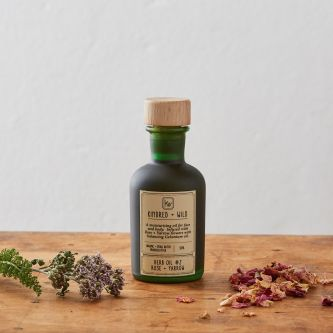An image of an organic rose oil in a green glass bottle created by the brand Kindred + Wild