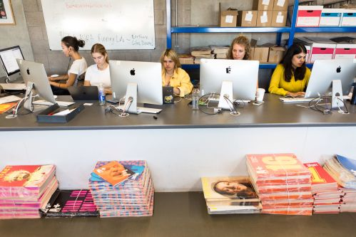 Students working at computers with piles of publications in the foreground