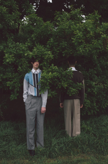 Photograph of two male models hiding under trees