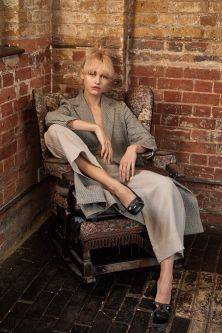 Model sitting on a chair modelling black leather mules