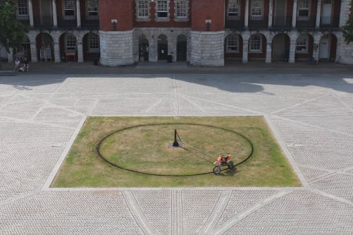 Drawing work using motorbike circling on Chelsea parade ground grass by Harley Cope.