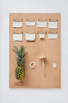 Wooden board with fabric, yarn and pineapple