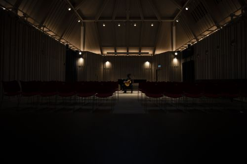 theatre in darkness with dim lights and man playing guitar on the  stage
