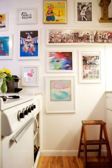 kitchen with paintings and photos hung up as though a gallery