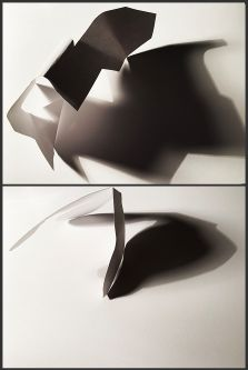Folded and cut paper casting long shadows, spatial design work.