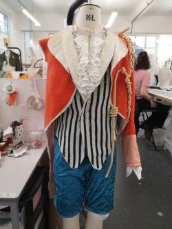 Photo of a partially made costume on a mannequin. The costume is made up of a red velvet jacket, striped waistcoat and blue trousers which are cropped at the knee.