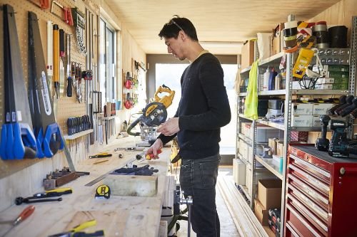 A person holding work tools in a workshop space