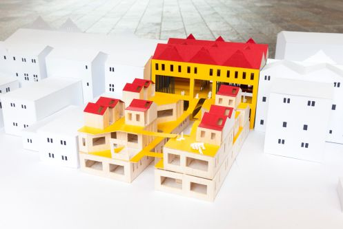 Two white models of houses either side of a bright yellow and red model.