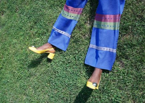 Model's legs in blue trousers against grass