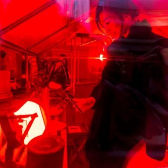A woman stood in a room which has been lit with a bright red light