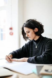 A young woman with black hair doing illutration