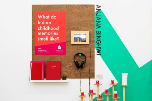 Degree show display by a student, on the topic of 'what do Indian childhood memories smell like?'. Headphones, two books and other interactive items are displayed on the wall for visitors to interact with.