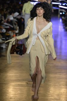 Woman walking down catwalk in biege and white