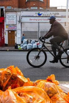 a man cycling past a pile of orange bin bags in the street