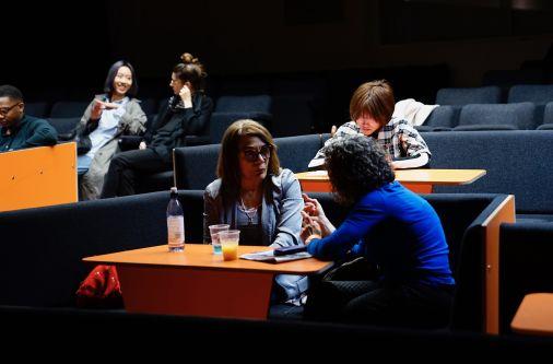 Students in dicussion in a dark lecture theatre