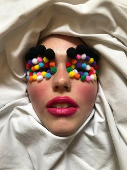 Close up of female model with multicoloured pom poms on eyelids and pink lipstick