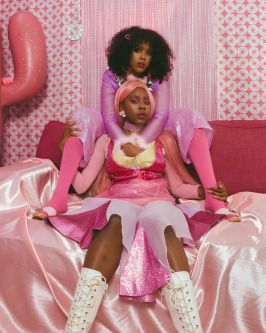 Photograph of two black models in a pink room wearing pink outfits
