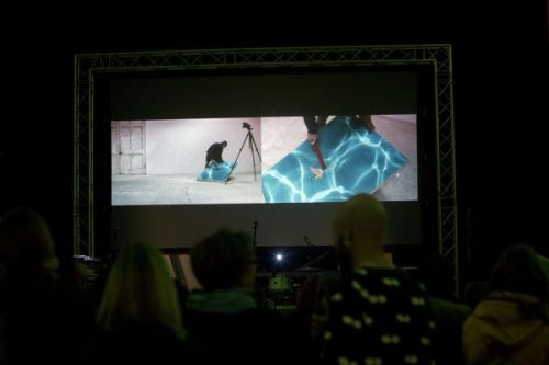 A photograph from behind a crowd watching a large screen above a stage as someone performs with a flat, square blue object on a split screen projection