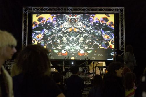 Photograph of a large screen above a stage showing a digital abstract graphic