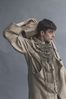 Male model wearing camel coat and crocheted necklace